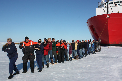 "Scientist aboard the USCG icebreaker Healy line up on the sea ice to ""tow"" the vessel. Credit: NASA/Kathryn Hansen"